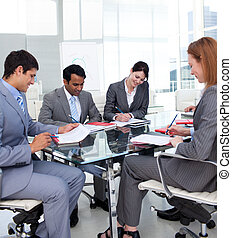 Multi-ethnic business people discussing a budget plan in a...