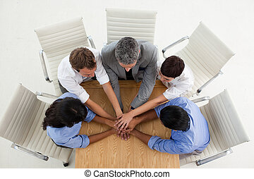 Multi-ethnic business people with hands together in a...