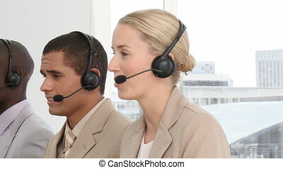 Multi-ethnic business people with headset on in a call-center