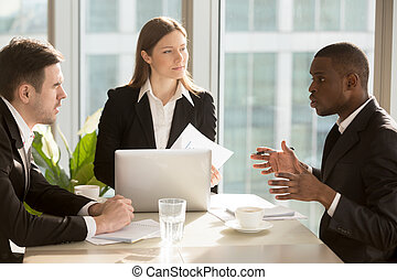 Multi-ethnic business team discussing project idea sitting at of