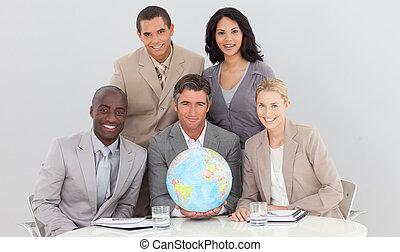 Multi-ethnic business team holding a terrestrial globe