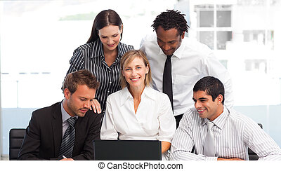 Multi-ethnic business team working with a laptop