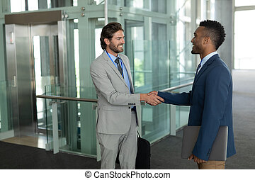 Multi-ethnic businessmen shaking hands with each other in the corridor