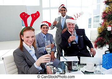 Multi-ethnic busioness team toasting with Champagne at a Christmas party in the office