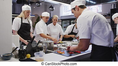 A group of professional multi-ethnic chefs wearing chefs whites in a busy restaurant kitchen, standing at a counter top and preparing food in slow motion