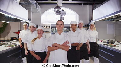 Multi-ethnic chefs wearing chefs whites in a restaurant ...