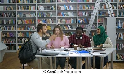 Multi ethnic college students meeting in library