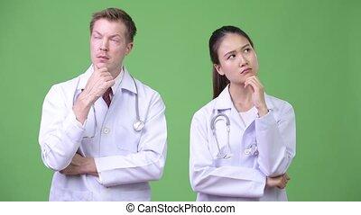 Multi-ethnic couple doctors thinking together - Studio shot...