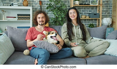 Multi-ethnic couple watching film on TV smiling caressing ...