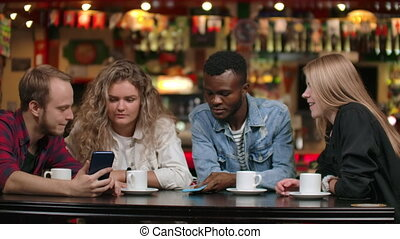 Multi-ethnic couples sitting in a cafe show photos to each other and laugh.