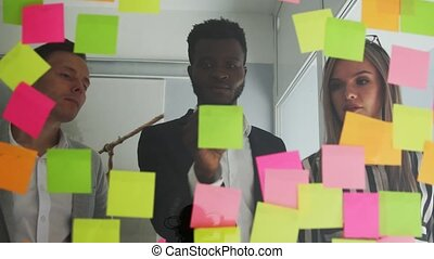 Multi ethnic creative team conducts brainstorming all their ideas are pasted on colored stickers on the glass wall. African American male and blonde team up in the office