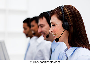 Multi-ethnic customer service agents with headset on in a...