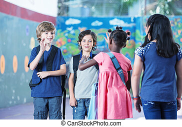 Multi ethnic elementary classroom kids greeting each other in th