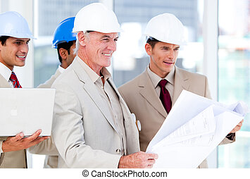 Multi-ethnic engineers studying plans in a building site