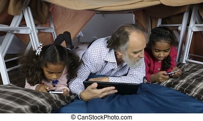 Multi-ethnic family using technology gadgets - Cheerful...
