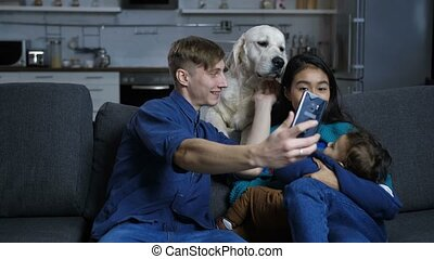 Multi ethnic family with pet dog posing for selfie -...
