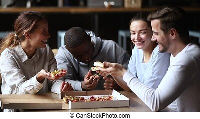 Multi ethnic friends spending time together chatting laughing eating pizza