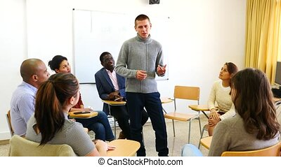 Multi-ethnic group of adult people sitting in circle and sharing ideas during class . High quality 4k footage