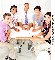 Multi-ethnic group of architects in a meeting smiling at the camera