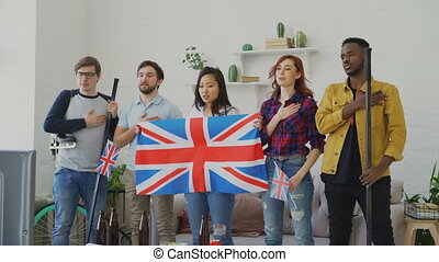 Multi ethnic group of friends listening and singing British...