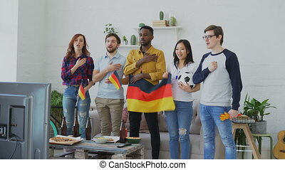 Multi-ethnic group of friends listening and singing German...