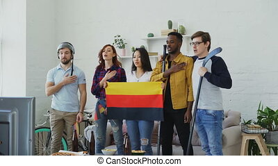 Multi ethnic group of friends listening and singing German...