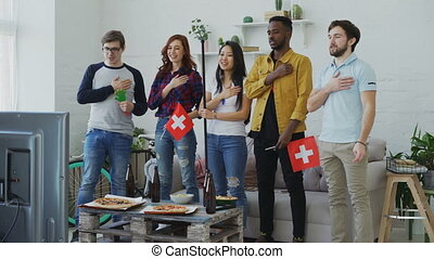 Multi ethnic group of friends listening and singing Swiss...