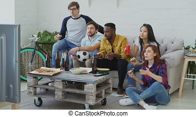 Multi-ethnic group of friends sports fans watching football championship on TV together eating pizza and drinking beer at home