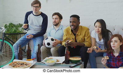 Multi ethnic group of friends sports fans watching football championship on TV together eating pizza and drinking beer at home