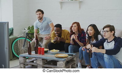 Multi ethnic group of friends sports fans watching sport event on TV together eating snacks and drinking beer at home indoors on holidays