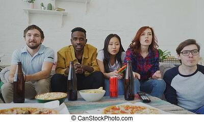 Multi ethnic group of friends sports fans watching sport match on TV together celebrating goal of favourite team while eating snacks and drinking beer