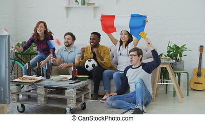 Multi-ethnic group of friends sports fans with French flags watching football championship on TV together at home and cheering up favourite team