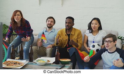 Multi-ethnic group of friends sports fans with German flags...