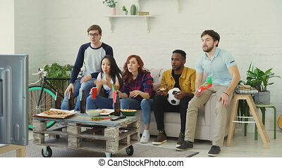 Multi-ethnic group of friends sports fans with Portuguese flags watching football championship on TV together at home indoors and cheering up favourite team