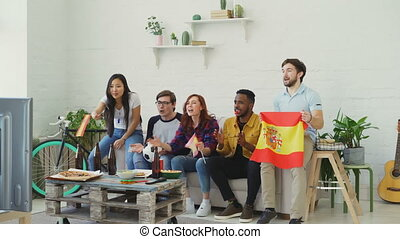 Multi-ethnic group of friends sports fans with Spainsh flags watching football championship on TV together at home indoors and cheering up favourite team
