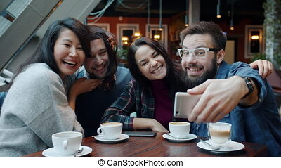 Multi-ethnic group of friends taking selfie in cafe using ...