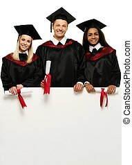 Multi ethnic group of graduated young students with blank notice board