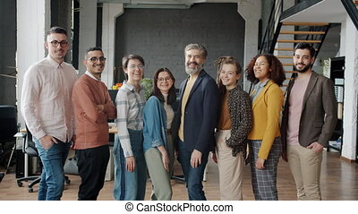 Multi-ethnic group of people colleagues are smiling laughing looking at camera at work in modern office. Businesspeople and workplace concept.