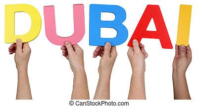 Multi ethnic group of people holding the word Dubai