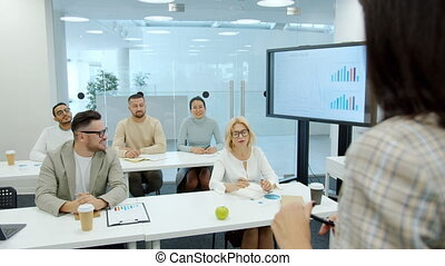 Multi-ethnic group of people listening to female business expert in office room