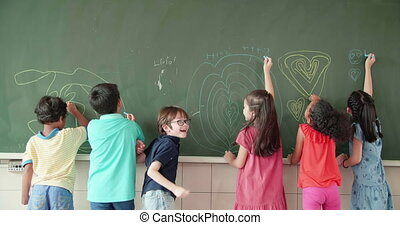 Multi-ethnic group of school children drawing on the ...