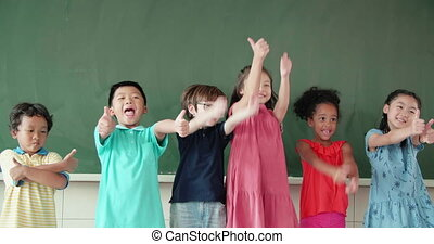 Multi-ethnic group of school children showing thumbs up in ...