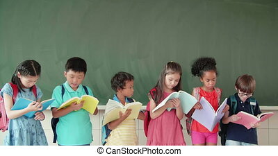 Multi-ethnic group of school children studying in classroom