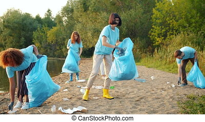 Multi-ethnic group of students collecting garbage from ...