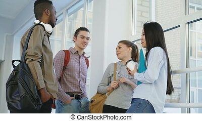 Multi-ethnic group of students is standing in wide corridor...