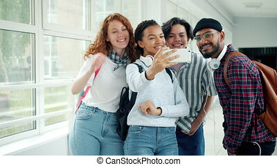 Multi-ethnic group of students taking selfie with smartphone...