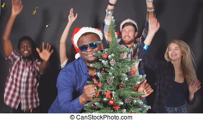 Multi ethnic group of young people at Christmas party in...