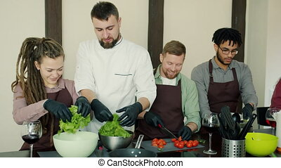 Multi-ethnic group of young people cooking salad during ...