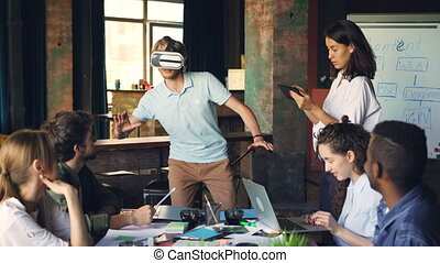 Multi-ethnic group of young people is having fun with augmented reality glasses, guy is using them moving hands and body, woman is working with tablet.