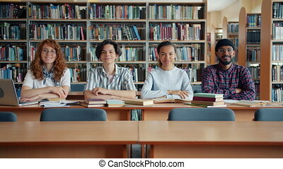 Multi-ethnic group of young people students sitting at desk ...